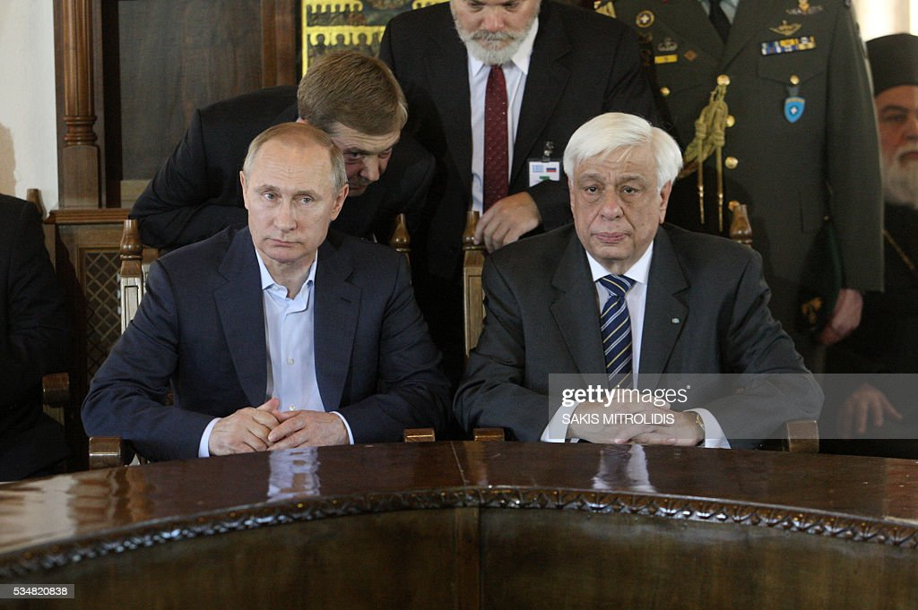 Russian President Vladimir Putin (L) poses next to Greek President Prokopis Pavlopoulos (R) during a visit to the monastic community of Mount Athos, in Karyes on May 28, 2016. Putin, who has often talked about his strong Orthodox faith, will join celebrations for the 1,000th anniversary of the Russian presence at the ancient, all-male monastic community of Mount Athos. The visit, Putin's first to the EU since December, comes at a low ebb in relations between Russia and Europe over the conflict in Ukraine that broke out in 2014, with sanctions still in force against Moscow. / AFP / SAKIS