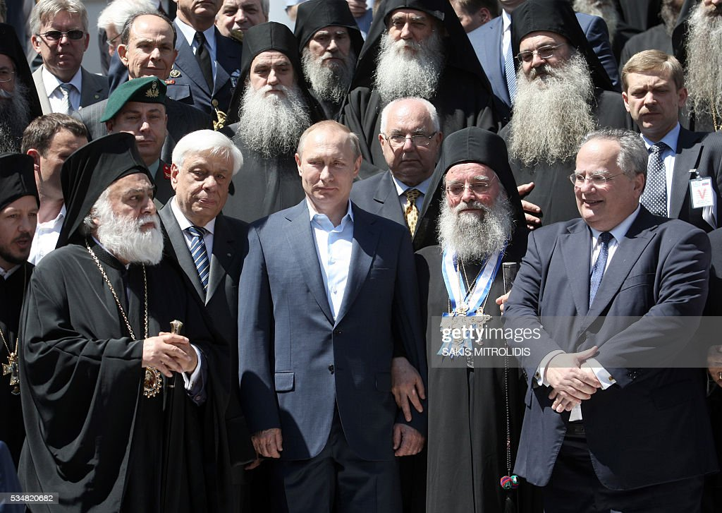 Russian President Vladimir Putin (C) poses with Greek President Prokopis Pavlopoulos (2R) during a visit in Karyes on May 28, 2016. Putin wraps up a two-day trip to Greece by visiting the monastic community of Mount Athos, one of Orthodox Christianity's holiest sites. Putin, who has often talked about his strong Orthodox faith, will join celebrations for the 1,000th anniversary of the Russian presence at the ancient, all-male monastic community of Mount Athos. / AFP / SAKIS