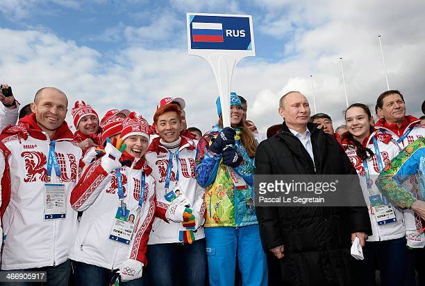 Russian President Vladimir Putin poses with Russian athletes while visiting the Coastal Cluster Olympic Village ahead of the Sochi 2014 Winter...