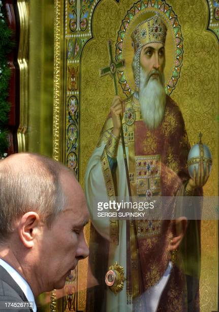 Russian President Vladimir Putin prays at an icon during a service and ceremony in Kiev on July 27 2013 to celebrate the 1025th anniversary of...