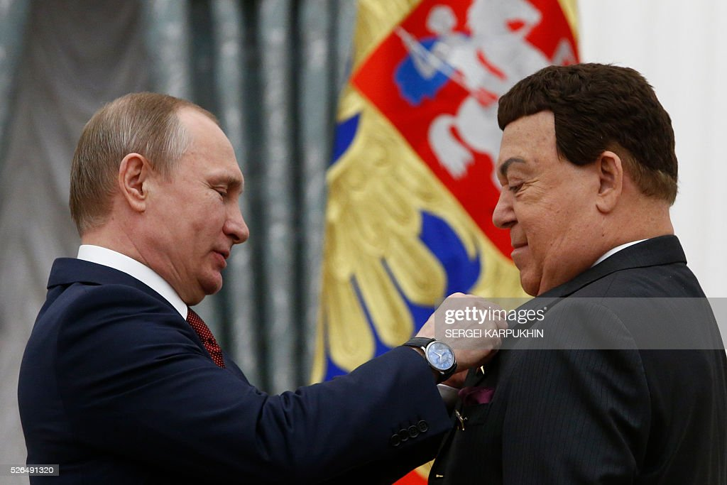 Russian President Vladimir Putin (L) presents Iosif Kobzon, Russian singer and deputy of the State Duma, Russia's lower house of Parliament, with the Hero of Labor medal during an awarding ceremony at the Kremlin in Moscow on April 30, 2016. / AFP / POOL / SERGEI