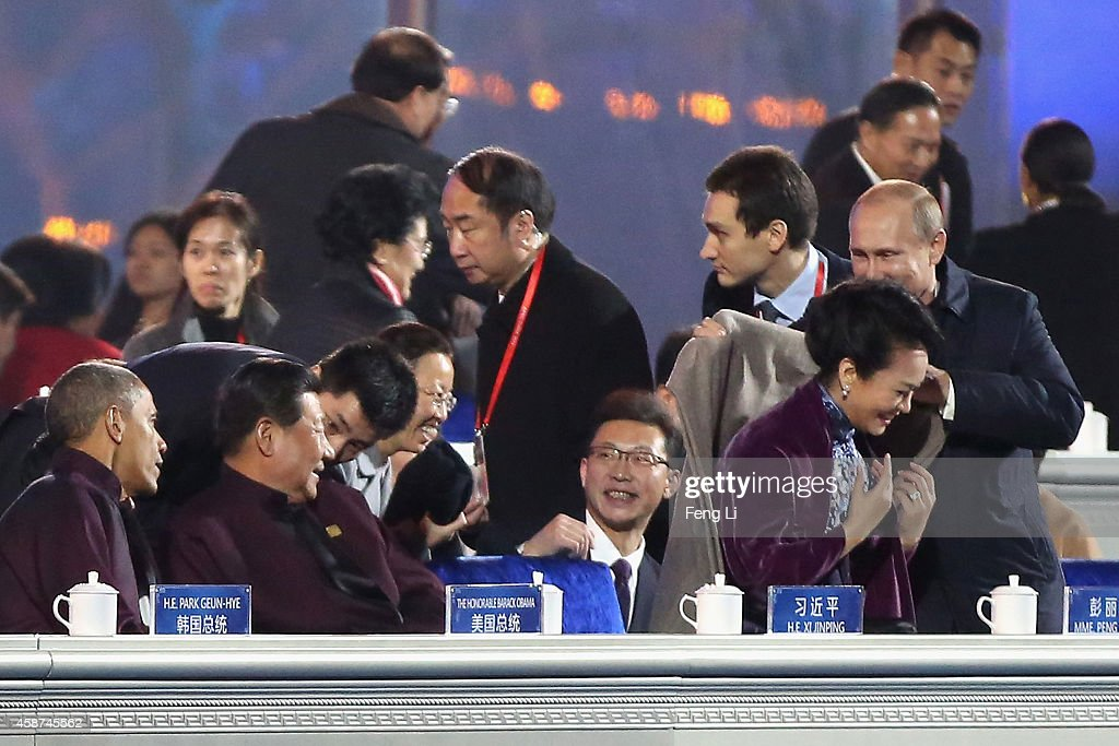 Russian President Vladimir Putin (R) puts on a shawl for Chinese President Xi Jinping's wife Peng Liyuan (2nd R) while Chinese President Xi Jinping (2nd L) and U.S. President Barack Obama (L) looks them before a fireworks show after the Welcome Banquet for 2014 APEC leaders at the National Aquatics Center, known as the Water Cube, on November 10, 2014 in Beijing, China. The 22nd APEC Economic Leaders' Meeting will hold on November 11, 2014 in Beijing, China.