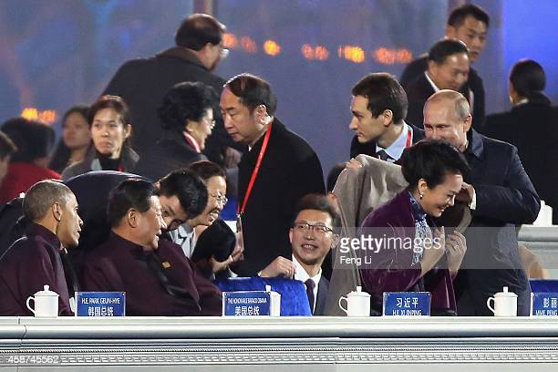 Russian President Vladimir Putin puts on a shawl for Chinese President Xi Jinping's wife Peng Liyuan while Chinese President Xi Jinping and US...