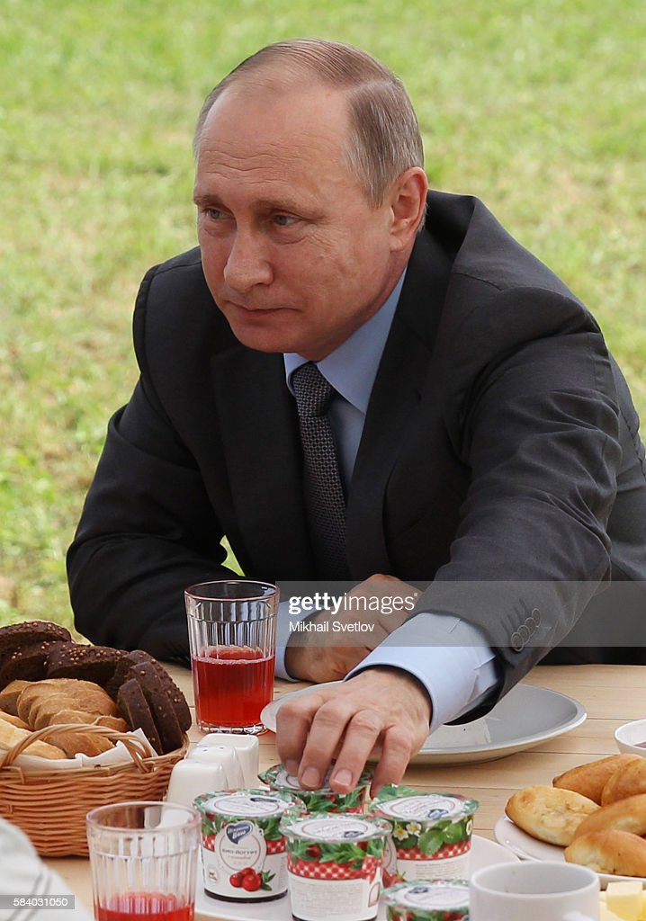 GORA RUSSIA JULY 28 Russian President Vladimir Putin reaches for a pot of yogurt during his meeting with farmers at the field in Dmitrova Gora...