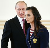 Russian President Vladimir Putin reacts as Russia's pole vaulter Yelena Isinbayeva passes by him during a reception in honour of members of the...