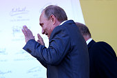 Russian President Vladimir Putin reacts as the drivers spray champagne on the podium after the Russian Formula One Grand Prix at Sochi Autodrom on...