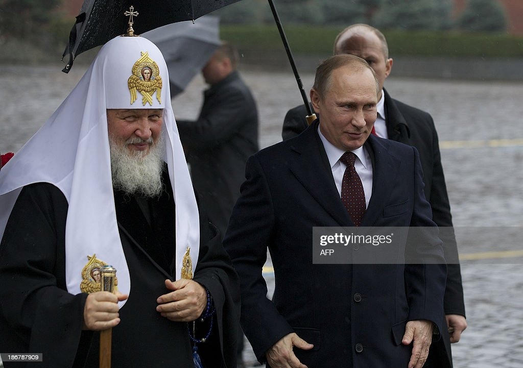 Russian President Vladimir Putin right walks with Russian Orthodox Church Patriarch Kirill left at the Red Square as they go to place flowers at a...
