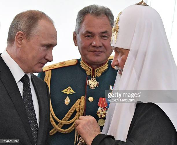Russian President Vladimir Putin Russian Patriarch Kirill of Moscow and Defence Minister Sergei Shoigu talk while visiting a marine church during...