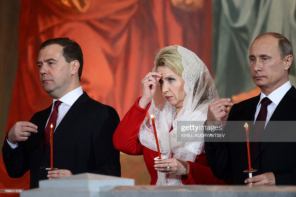 Russian President Vladimir Putin (R), Russian Prime Minister Dmitry Medvedev (L) and his wife Svetlana, attend an Orthodox Easter celebration at the Cathedral of Christ the Savior in Moscow in the first hours of May 5, 2013.
