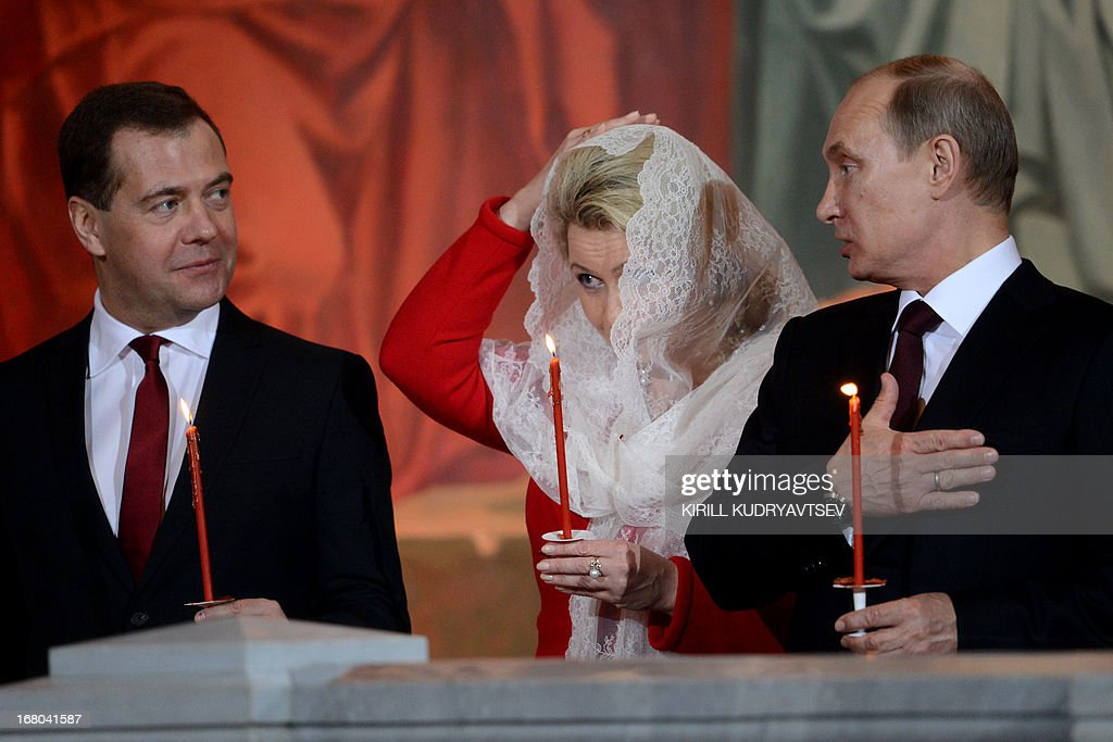 Russian President Vladimir Putin (R), Russian Prime Minister Dmitry Medvedev (L) and his wife Svetlana attend Orthodox Easter celebrations at the Christ the Saviour Cathedral in Moscow early on May 5, 2013. AFP PHOTO/KIRILL KUDRYAVTSEV