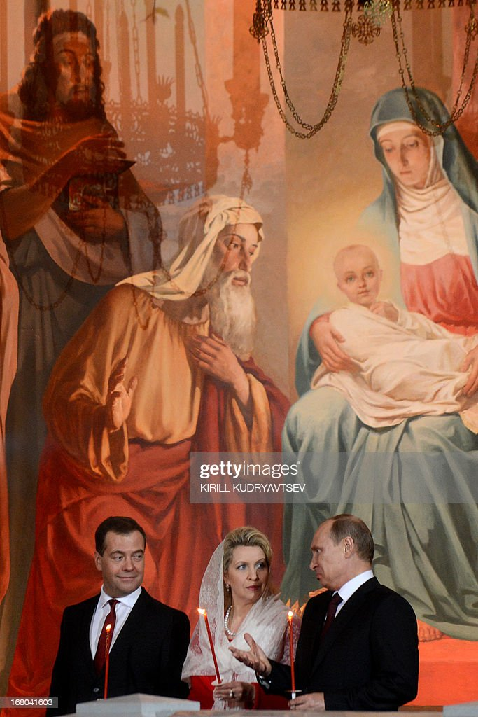 Russian President Vladimir Putin (R), Russian Prime Minister Dmitry Medvedev (L) and his wife Svetlana attend Orthodox Easter celebrations at the Christ the Saviour Cathedral in Moscow early on May 5, 2013.