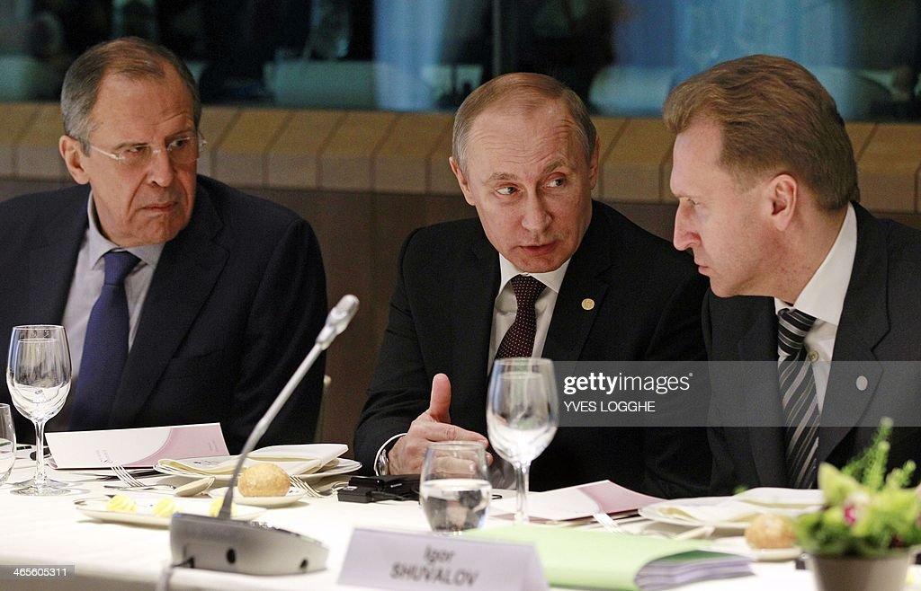 Russian President Vladimir Putin (C), Russia's vice Prime Minister Igor Ivanovich Shuvalov (R) and Russia's Foreign Minister Sergey Lavrov talk to each other during a meeting at the European Council building in Brussels on January 28, 2014. Russian President Vladimir Putin and the EU's top officials went into talks on January 28 sharply divided over Ukraine and eastern Europe, with trust in short supply and little sign of compromise. AFP PHOTO / POOL / Yves Logghe