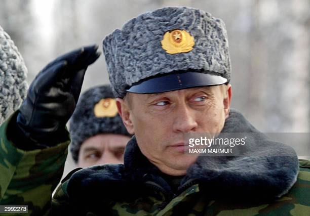 Russian President Vladimir Putin salutes officers 18 February 2004 shortly after his arrival at the observation point of the Artic cosmodrome in...