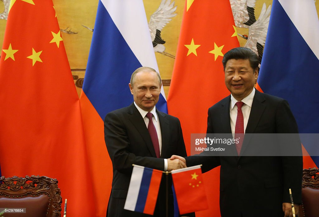 Russian President Vladimir Putin (L) shake hands with Chinese President Xi Jinping (R) during their meeting in June 25, 2016 in Beijing, China. Vladimir Putin is having a state visit to China.