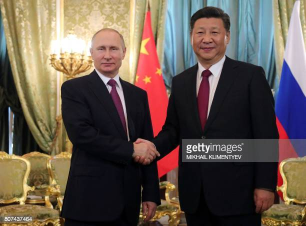 Russian President Vladimir Putin shakes hands with Chinese Leader Xi Jinping during their meeting in Moscow on July 4 2017 Russian President Vladimir...
