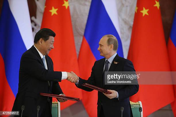 Russian President Vladimir Putin shakes hands with Chinese President Xi Jinping during their joint press conference in the Grand Kremlin Palace on...