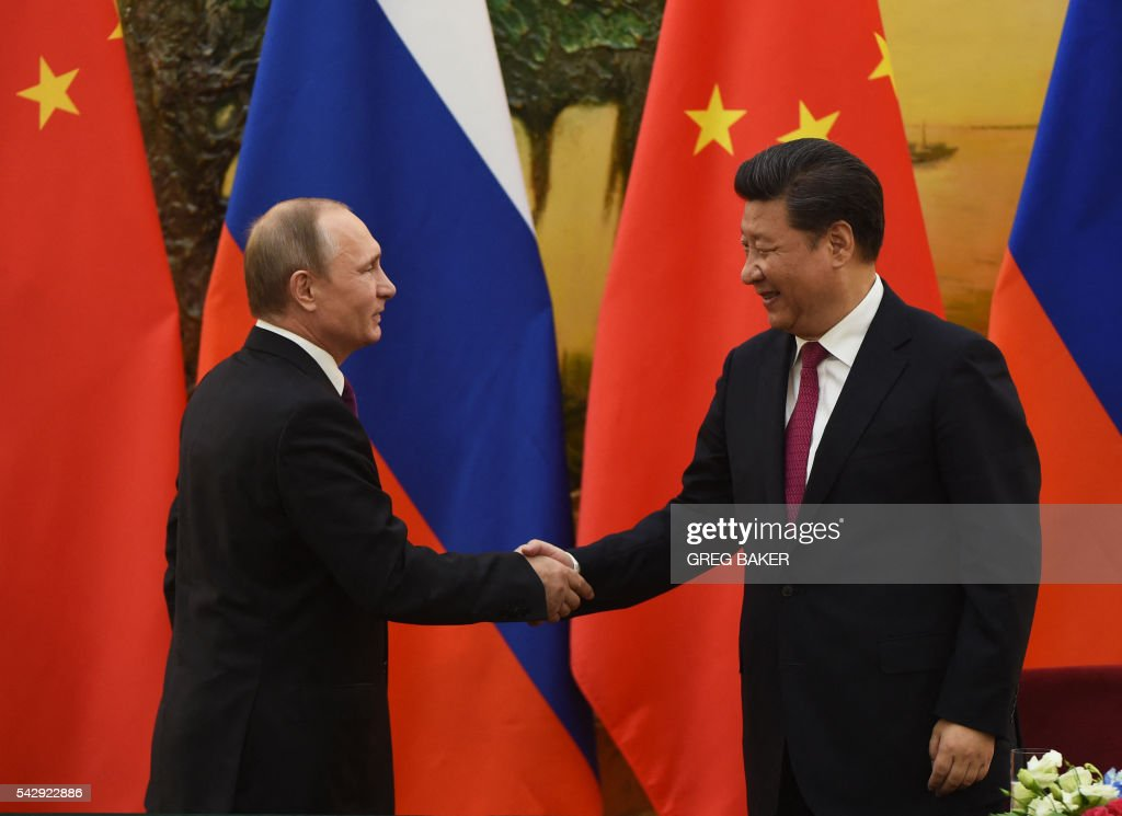 Russian President Vladimir Putin (L) shakes hands with Chinese President Xi Jinping at the end of a joint press briefing in Beijing's Great Hall of the People on June 25, 2016. / AFP / POOL / GREG