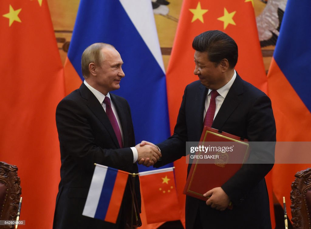 Russian President Vladimir Putin (L) shakes hands with Chinese President Xi Jinping during a signing ceremony in Beijing's Great Hall of the People on June 25, 2016. / AFP / POOL / GREG