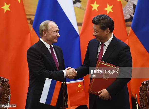 Russian President Vladimir Putin shakes hands with Chinese President Xi Jinping during a signing ceremony in Beijing's Great Hall of the People on...