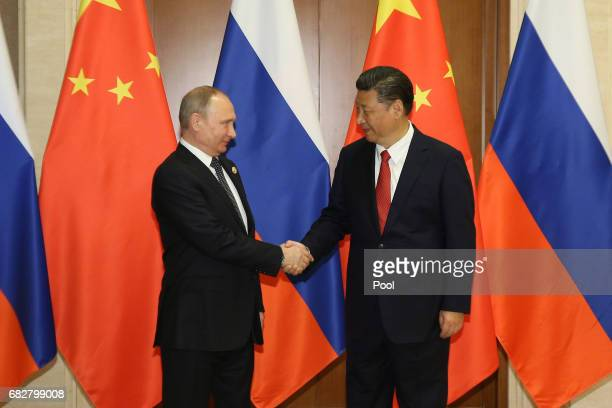 Russian President Vladimir Putin shakes hands with Chinese President Xi Jinping ahead a bilateral meeting at Diaoyutai State Guesthouse in Beijing...
