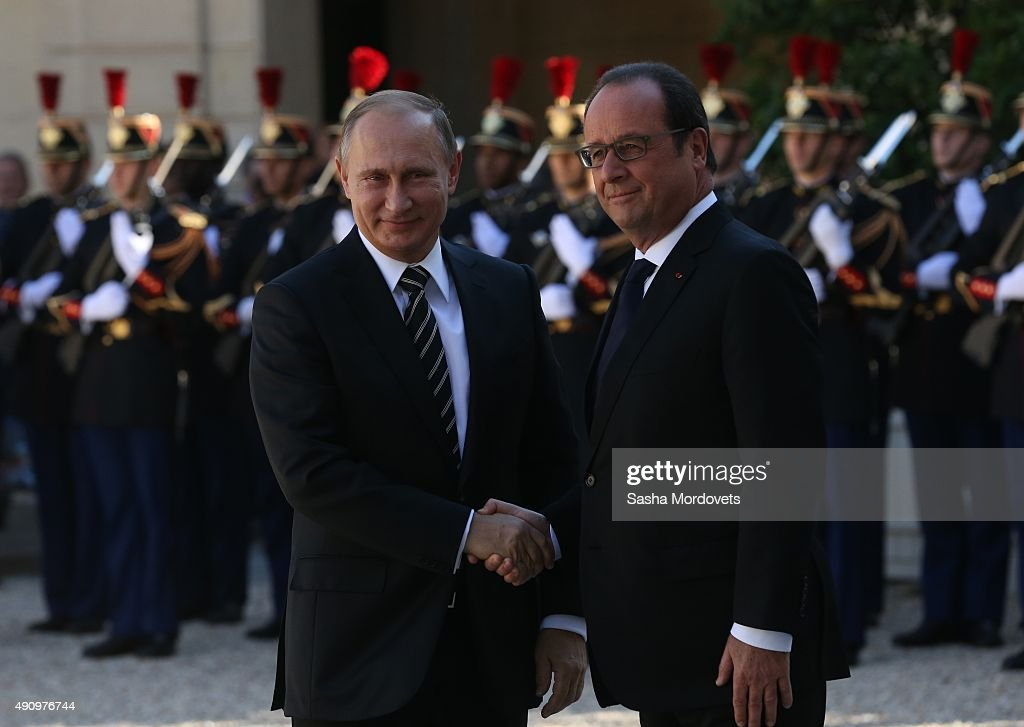Russian President Vladimir Putin shakes hands with French President Francois Hollande prior to their meeting at the Elysee Presidential Palace on...