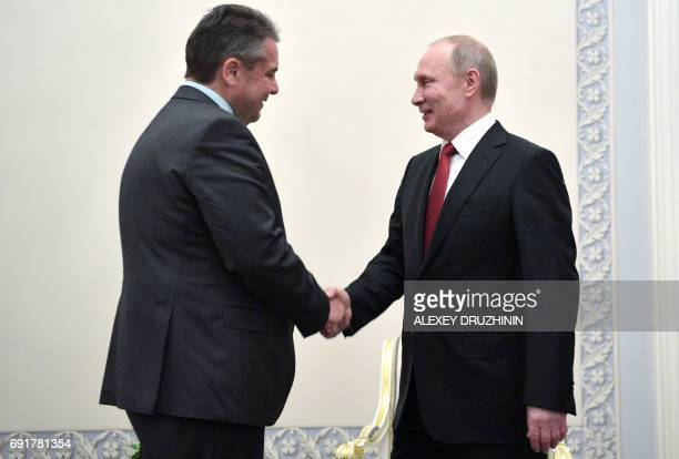 Russian President Vladimir Putin shakes hands with German Foreign Minister Sigmar Gabriel on the sidelines of the Saint Petersburg International...