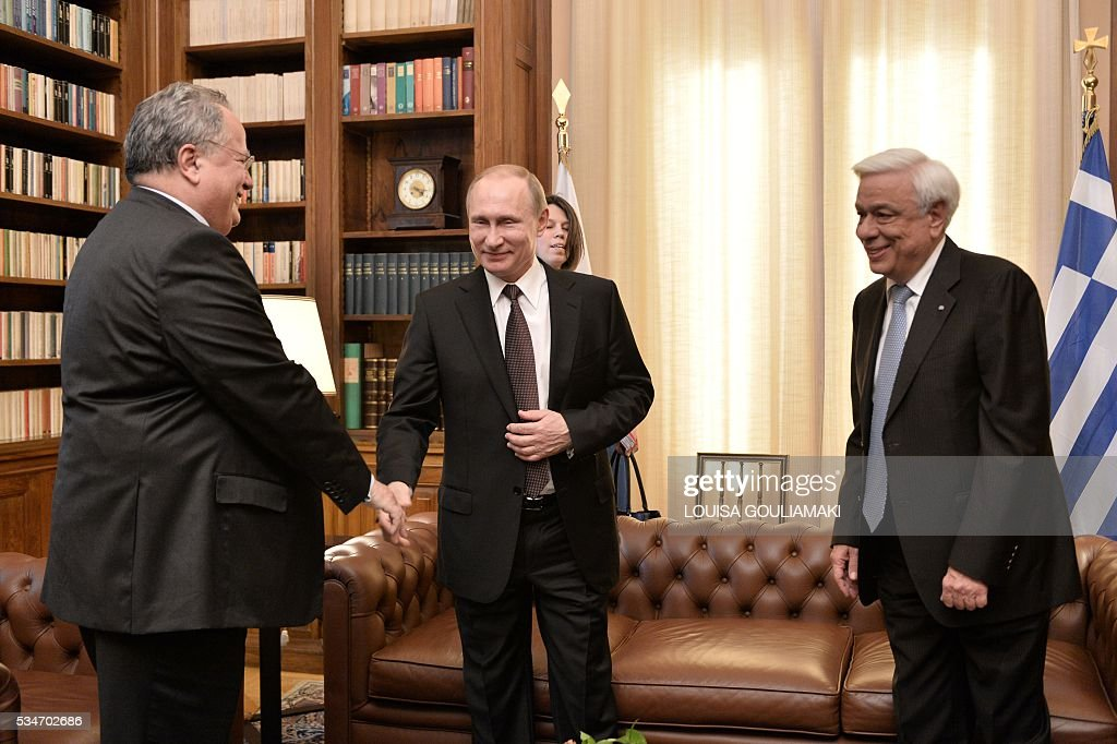 Russian President Vladimir Putin (C) shakes hands with Greek Foreign Affairs minister Nikos Kotzias (L) prior to a meeting with his Greek President Prokopis Pavlopoulos (R) during a meeting at the Presidential Palace on May 27, 2016, in Athens. The visit -- Putin's first to the EU since December -- comes as the bloc's leaders are to discuss next month whether to renew sanctions on Russia's banking, defence and energy sectors that expire in July. / AFP / POOL / LOUISA