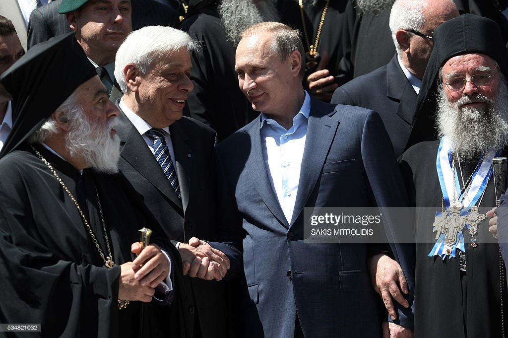 Russian President Vladimir Putin (C) shakes hands with Greek President Prokopis Pavlopoulos (L)during a visit to the monastic community of Mount Athos, in Karyes on May 28, 2016. Putin, who has often talked about his strong Orthodox faith, will join celebrations for the 1,000th anniversary of the Russian presence at the ancient, all-male monastic community of Mount Athos. The visit, Putin's first to the EU since December, comes at a low ebb in relations between Russia and Europe over the conflict in Ukraine that broke out in 2014, with sanctions still in force against Moscow. / AFP / SAKIS