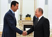 Russian President Vladimir Putin shakes hands with his Syrian counterpart Bashar alAssad during their meeting at the Kremlin in Moscow on October 20...