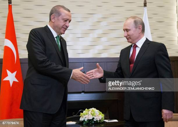 Russian President Vladimir Putin shakes hands with his Turkish counterpart Recep Tayyip Erdogan during their meeting at the Bocharov Ruchei state...