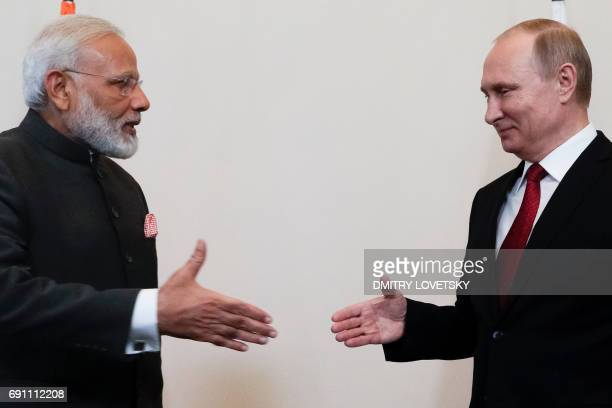 Russian President Vladimir Putin shakes hands with Indian Prime Minister Narendra Modi during a meeting on the sidelines of the St Petersburg...