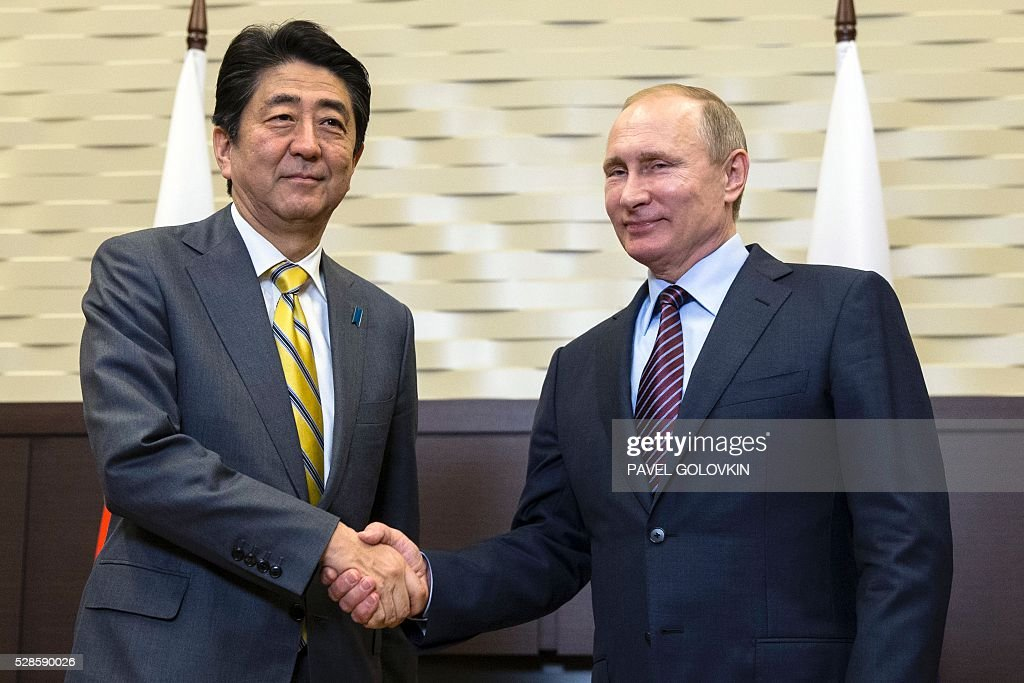 Russian President Vladimir Putin (R) shakes hands with Japanese Prime Minister Shinzo Abe during a meeting at the Bocharov Ruchei state residence in Sochi on May 6, 2016. / AFP / POOL / Pavel Golovkin