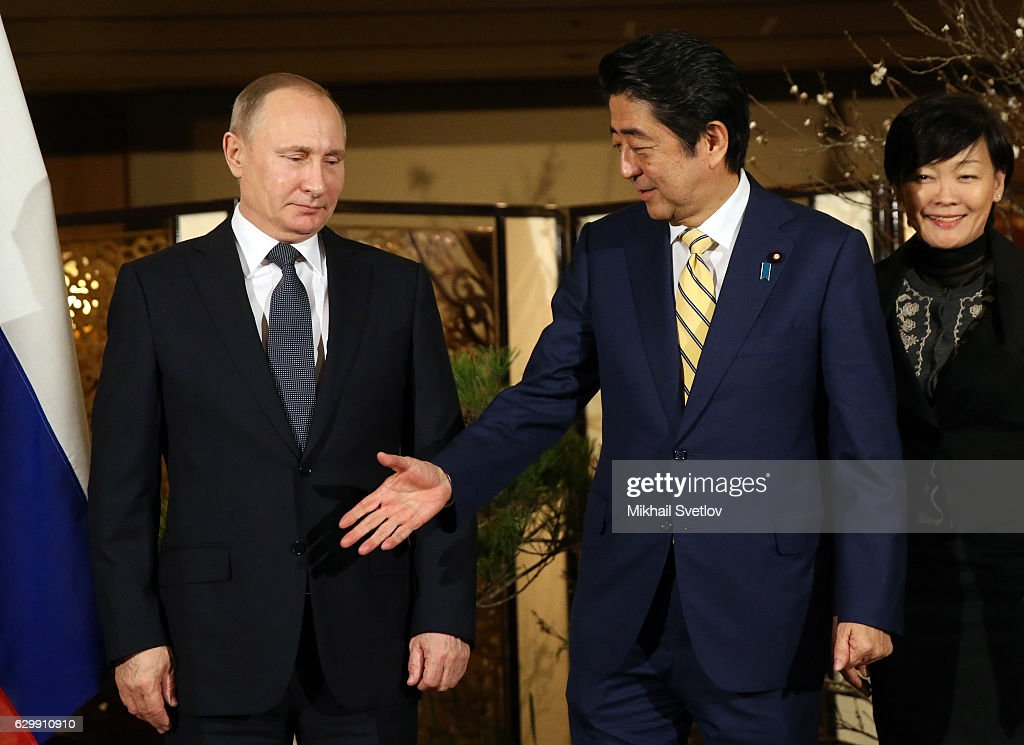 Russian President Vladimir Putin (L) shakes hands with Japanese Prime Minister Shinzo Abe (C) as his wife Akie Abe (R) looks on during the official reception ceremony on December 15, 2016 in Nagato, Japan. The Russian president is on a two-days visit to Japan.