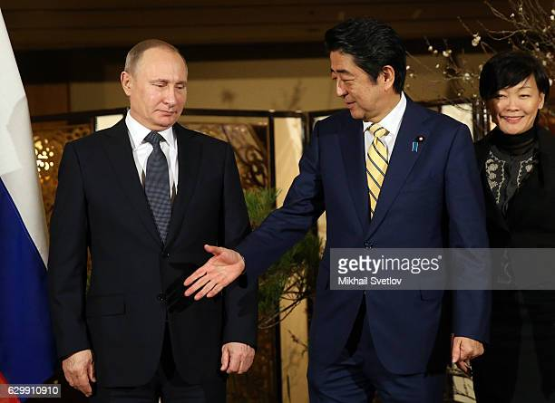 Russian President Vladimir Putin shakes hands with Japanese Prime Minister Shinzo Abe as his wife Akie Abe looks on during the official reception...