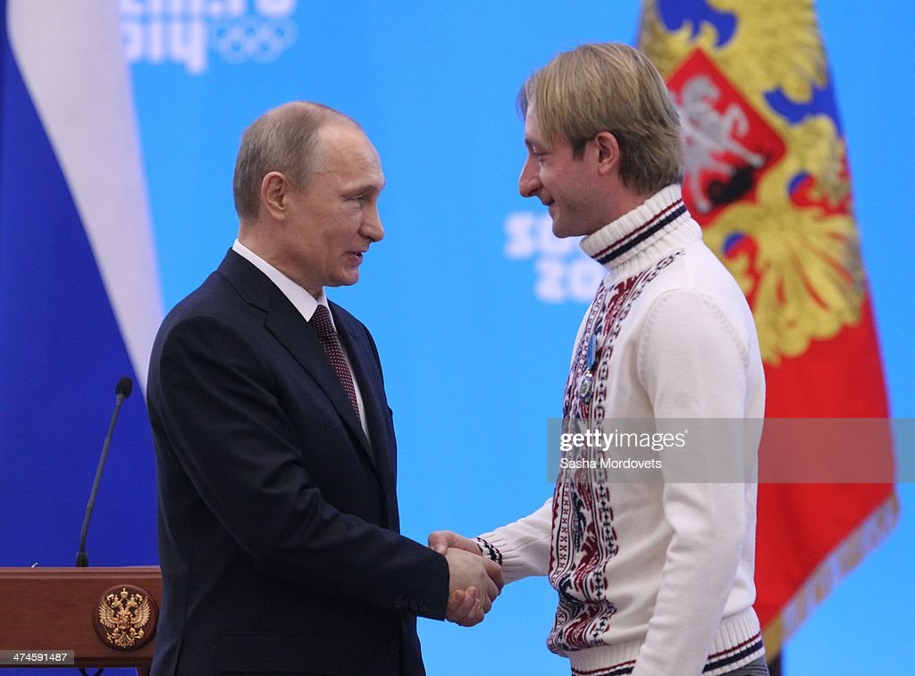 Russian President Vladimir Putin shakes hands with Olympic gold medalist in figure skating Evgeni Plushenko after presenting him with an award during...
