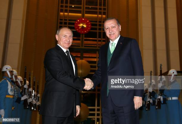 Russian President Vladimir Putin shakes hands with President of Turkey Recep Tayyip Erdogan during an official welcoming ceremony at Presidential...