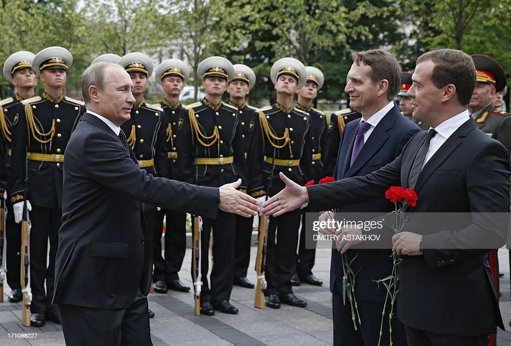 Russian President Vladimir Putin (L) shakes hands with Prime Minister Dmitry Medvedev (R) during laying wreath ceremony at the Unknown Soldier Tomb in Moscow on June 22, 2013. Russians mark the Day of Memory and Mourning of Nazi Germany's attack of the former Soviet Union on the dawn of June 22, 1941. The Great Patriotic War, 1941-1945, started exactly at four o'clock in the morning 72 years ago to the day.