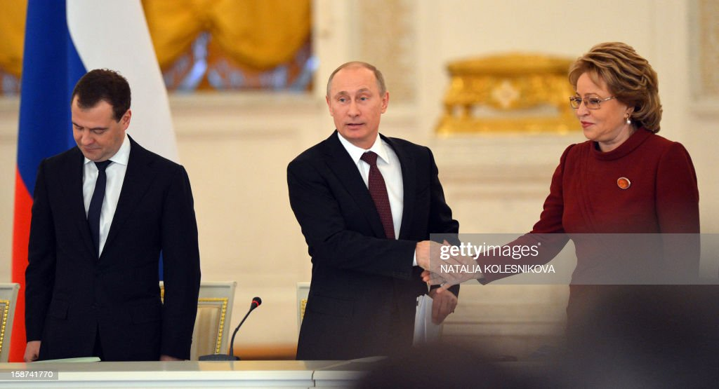 Russian President Vladimir Putin (C) shakes hands with Russia's upper house, Federation Council, speaker Valentina Matviyenko during a State Council meeting at the Kremlin, in Moscow, on December 27, 2012, with Prime Minister Dmitry Medvedev (L). Putin told today a meeting of top officials in the Kremlin he intended to sign into law a bill banning Americans from adopting Russian children that has raised tensions between Moscow and Washington. AFP PHOTO / POOL/ NATALIA KOLESNIKOVA