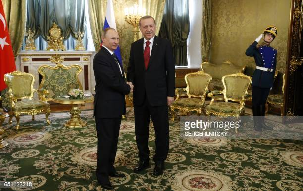 TOPSHOT Russian President Vladimir Putin shakes hands with Turkey's President Recep Tayyip Erdogan ahead of their meeting in the Kremlin in Moscow on...