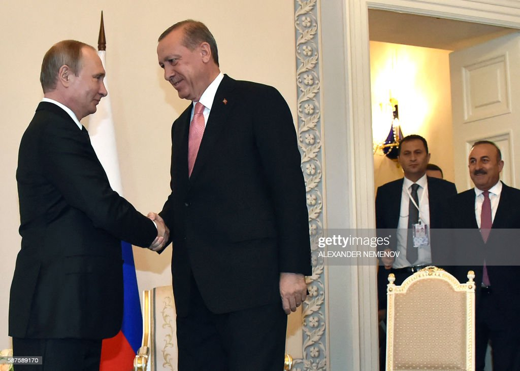 Russian President Vladimir Putin shakes hands with Turkish President Recep Tayyip Erdogan as Turkish Foreign Affairs Minister Mevlut Cavusoglu looks...