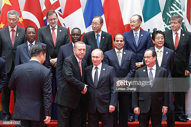 Russian President Vladimir Putin shakes hands with Turkish President Recep Tayyip Erdogan before a group photo at the Hangzhou International Expo...