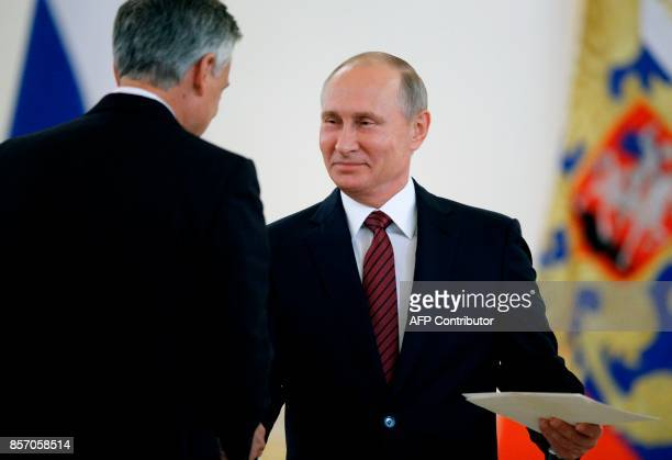 Russian President Vladimir Putin shakes hands with US ambassador to Russia Jon Huntsman after receiving his credentials during a ceremony at the...