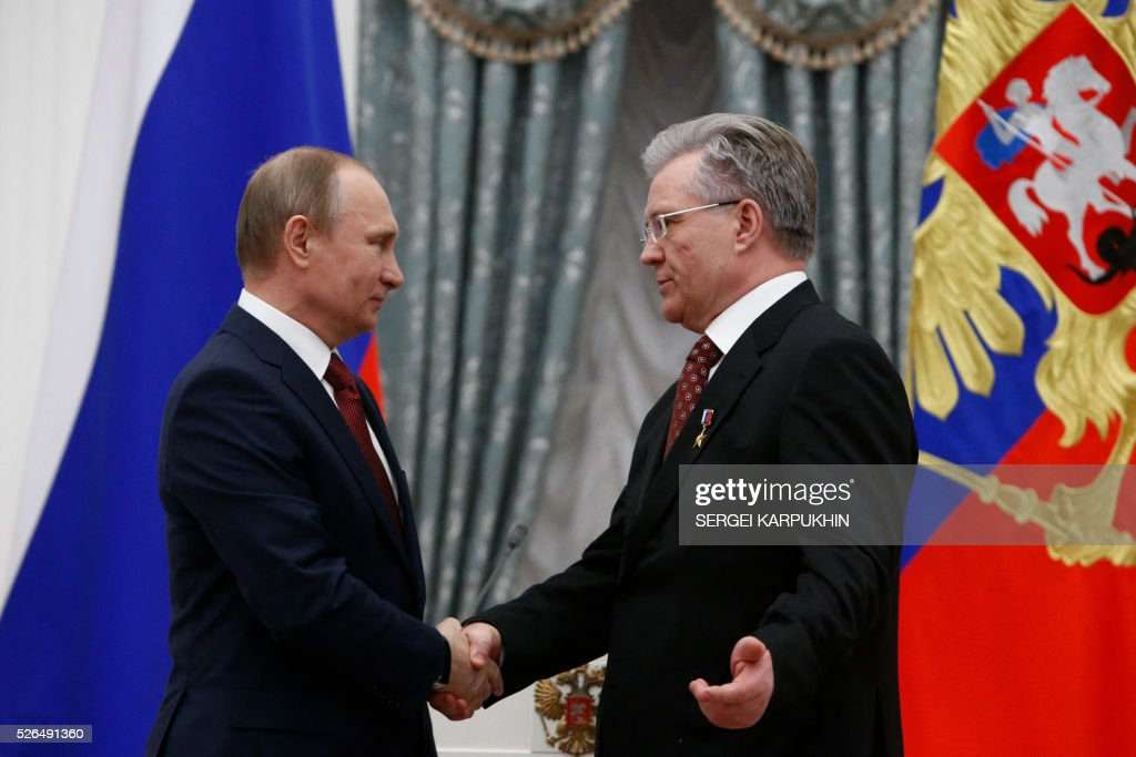 Russian President Vladimir Putin (L) shakes hands with Vladimir Bogdanov, Director General of Surgutneftegas oil company, during an awarding ceremony at the Kremlin in Moscow on April 30, 2016. / AFP / POOL / SERGEI
