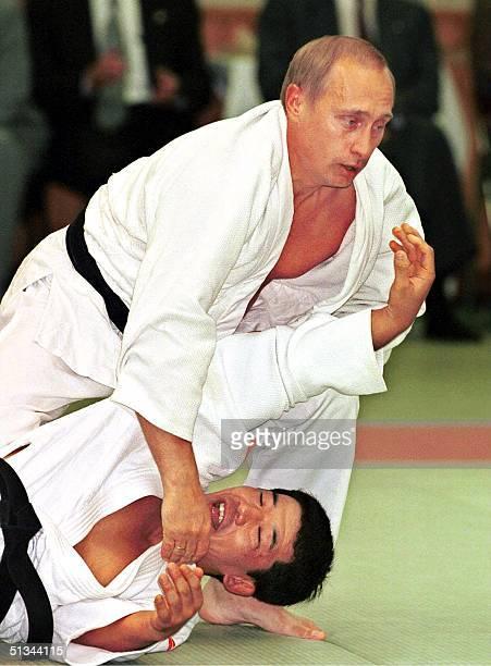 Russian President Vladimir Putin shows off his judo skills against a Japanese opponent at a Tokyo judo training center 05 September 2000 Putin left...