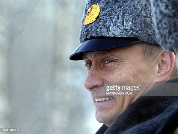 Russian President Vladimir Putin smiles 18 February 2004 as he watches the launch of spacecraft Molnia carrying a military spy satelite on board from...