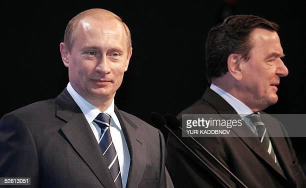 Russian President Vladimir Putin smiles as German Chancellor Grehard Schroeder stands next to him during the opening ceremony of the Russian Hall at...