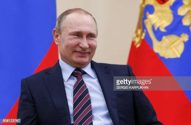 Russian President Vladimir Putin smiles during a meeting with representatives of business community at the NovoOgaryovo state residence outside...