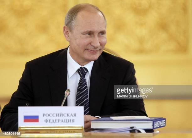 Russian President Vladimir Putin smiles during the Supreme Eurasian Economic Council meeting at the Kremlin in Moscow on December 23 2014 Russian...