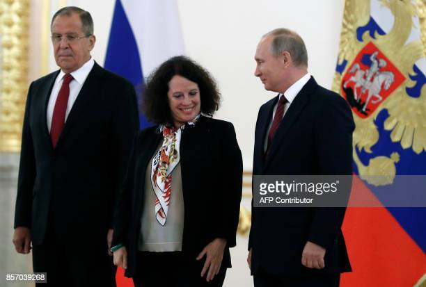 Russian President Vladimir Putin smiles to France's ambassador to Russia Sylvie Bermann as they and Foreign Minister Sergei Lavrov pose for a photo...