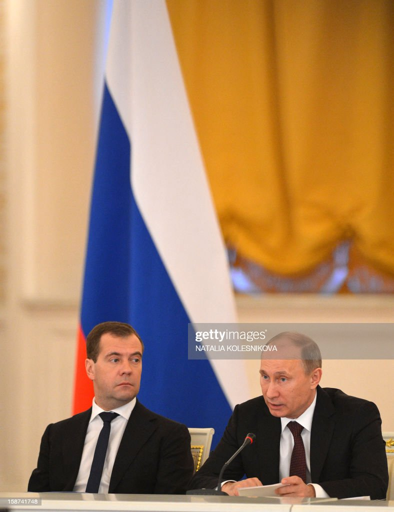 Russian President Vladimir Putin (R) speaks alongside Prime Minister Dmitry Medvedev during a State Council meeting at the Kremlin, in Moscow, on December 27, 2012. Putin told today a meeting of top officials in the Kremlin he intended to sign into law a bill banning Americans from adopting Russian children that has raised tensions between Moscow and Washington.